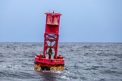 Red Ocean Buoy. A close-up photo of a red ocean buoy floating in the water near a harbor. There is a bell and barnacles have grown to the bottom of the buoy royalty free stock photography