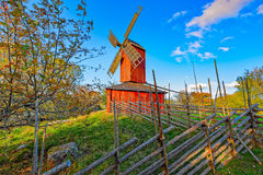 Red ochre colour wooden windmill. In a old vintage rural landscape at Aland islands, Finland. Jan Karlsgarden open air museum Royalty Free Stock Image