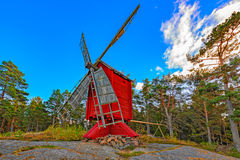 Red ochre colour wooden windmill. In a old vintage rural landscape at Aland islands, Finland. Jan Karlsgarden open air museum Royalty Free Stock Photography
