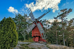 Red ochre colour wooden windmill. In a old vintage rural landscape at Aland islands, Finland. Jan Karlsgarden open air museum Stock Photography