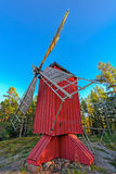 Red ochre colour wooden windmill. In a old vintage rural landscape at Aland islands, Finland. Jan Karlsgarden open air museum Royalty Free Stock Photo