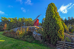 Red ochre colour wooden windmill. In a old vintage rural landscape at Aland islands, Finland. Jan Karlsgarden open air museum Stock Image