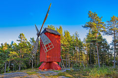 Red ochre colour wooden windmill. In a old vintage rural landscape at Aland islands, Finland. Jan Karlsgarden open air museum Royalty Free Stock Images