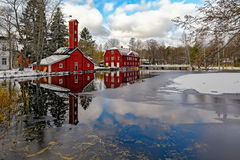 Red ochre old wooden houses over pond Royalty Free Stock Images