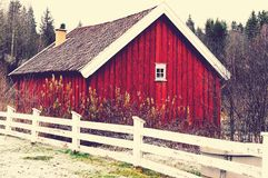 Red od wooden barn. Old wooden barn. White fence in front of the building. Building in an old foundry in Baerum Verk. Vintage look from HDR photo. Norwegian Stock Photo