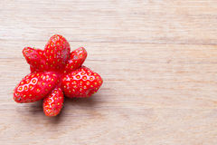 Red odd strawberry fruit on wooden table. Royalty Free Stock Image