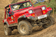 Red off-road car in difficult terrain Stock Images
