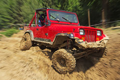 Red off-road car in difficult terrain Royalty Free Stock Image