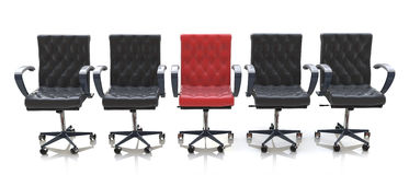 Red office chair among black chairs  on white background Royalty Free Stock Photos