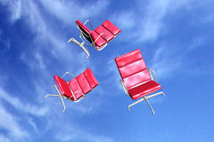 Red office chairs over blue sky Royalty Free Stock Photos