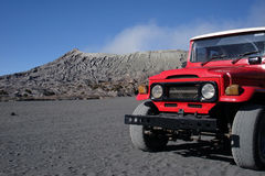 Red offroad car. On volcano background. Bromo. Java island. Indonesia Stock Photos