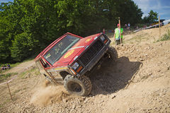 Red offroad car is in great lateral tilt Royalty Free Stock Photography