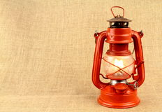 Red oil lamp on burlap . Vintage concept. Royalty Free Stock Photo