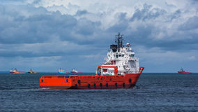 Red Oil Platform Supply Ship. Red supply vessel going out to sea Royalty Free Stock Image
