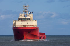 Red Oil Rig Supply Ship. Supply vessel at harbour entrance Stock Images