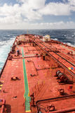 Red oil tanker proceeding to skyline. Crude oil tanker deck with green stripe Royalty Free Stock Photography