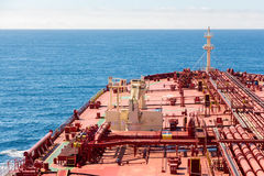 Red oil tanker proceeding to skyline. Crude oil tanker deck with green stripe Royalty Free Stock Images