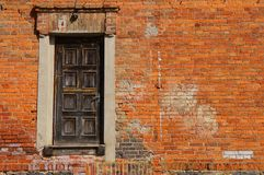 Red old Brick Wall with a black door. Old factur. Red Brick Wall with a old black door. Bricks. Red. Background Royalty Free Stock Photography
