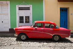 Red old car in front of colourful houses, Cuba royalty free stock photo