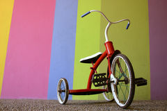 Red Old Childrens Bike in front of a Bright Colored Wall Stock Photos