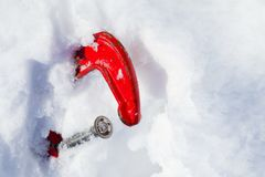 The red old clamp in the snow. Symbol of snow drifts, snowfall, avalanches, snow losses, work in the cold. Copy space.  Royalty Free Stock Photo