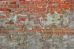 Red old dirty brick wall background. Old damaged brick wall with plaster Royalty Free Stock Photography