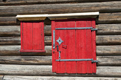 Red old door and window on the wooden wall of a village house. Excellent background. Stock Photography