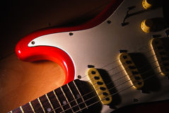 Red Old electric guitar against wood background. Royalty Free Stock Photos
