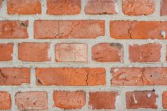 Red old faded bricks wall background with cracks and flaws. On it surface stock photos