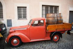 Red old fashioned pickup truck. Retro farm pickup truck with old wooden barrels. Old red car on the street Royalty Free Stock Photo