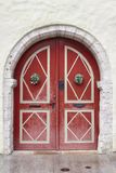 Red old fashioned wooden door on white facade. Tallinn Royalty Free Stock Photo