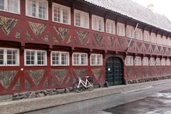 Red old house with white windows - half-timbered house made of wood and bricks. Bicycle near the wall stock photos