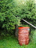 Red old iron barrel for petroleum products, used, used to collect water for watering the garden, against the green background Royalty Free Stock Photography