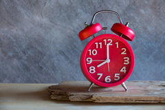 Red old retro style alarm clock on wood table Royalty Free Stock Photo