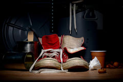 Red old sneakers from a garbage. Royalty Free Stock Photo