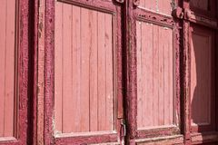 Red old street door with peeled paint in daylight. The door is an old wooden red color with peeling paint is illuminated by the bright summer sun stock images