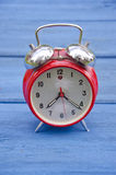 Red old style alarm clock on garden table Royalty Free Stock Images