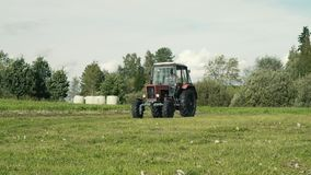 Red old tractor in farmyard driving towards stock footage