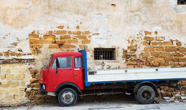 Red old truck. An functional classic truck in front of an aged wall, giving the perfect pair Stock Photos