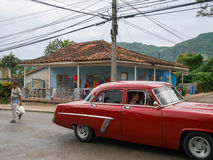 Red old vintage american cars in cuba streets. Hot summer day where tourists are siting in a beautiful luxury car and enjoying views of CUba. Cheap taxi in retro Stock Image
