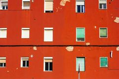 Red old wall of a house with many windows Royalty Free Stock Photos