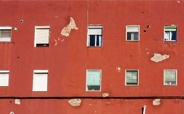 Red old wall of a house with many windows Stock Images