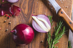 Red onion bulb on brown cutting board. Royalty Free Stock Photos