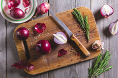 Red onion bulb on brown cutting board. Royalty Free Stock Photography