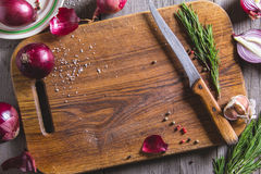 Red onion bulb on brown cutting board. Stock Image