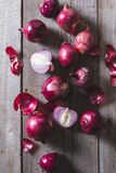 Red onion bulbs lying on an old wooden table. Stock Photography