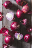 Red onion bulbs lying on an old wooden table. Stock Photo