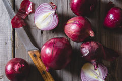 Red onion bulbs lying on an old wooden table. Stock Images