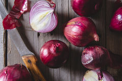 Red onion bulbs lying on an old wooden table. Royalty Free Stock Images