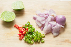 Red onion chopped, chilli chopped  and lemon. On wooden chopping board Royalty Free Stock Photo